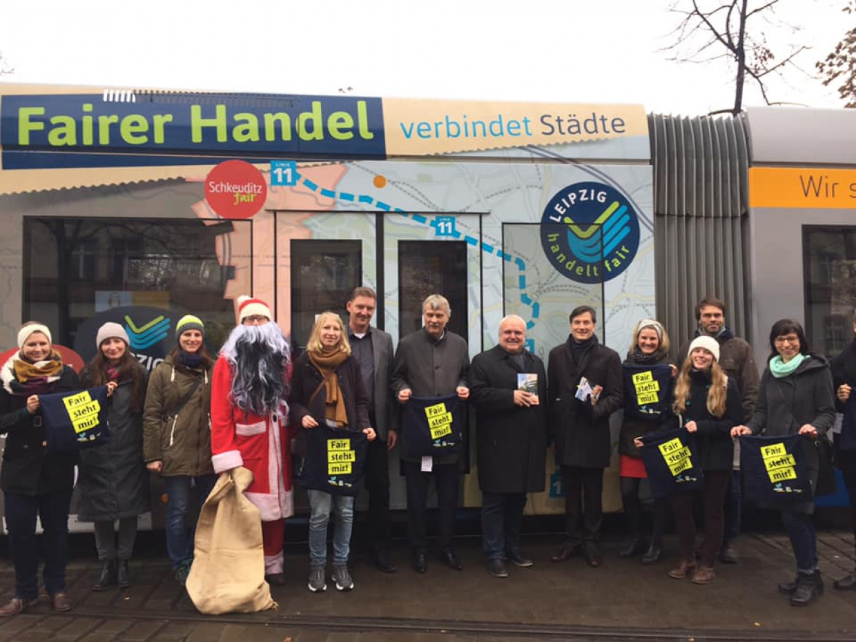 Das Leipzig handelt fair Team mit einem großen Stoffaufsteller, welcher das Logo des Vereins zeigt, stehen vor dem Leipziger Rathaus. Sie schauen freundlich in die Kamera.